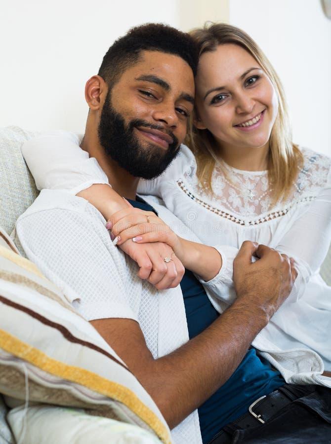 年轻在家拥抱在长沙发的金发碧眼的女人和男朋友 库存照片