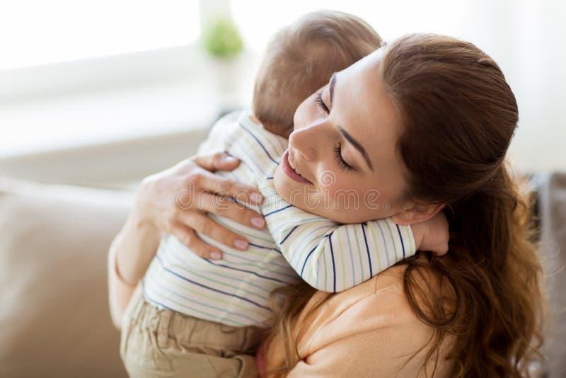 在家拥抱小婴孩的愉快的年轻母亲 免版税图库摄影