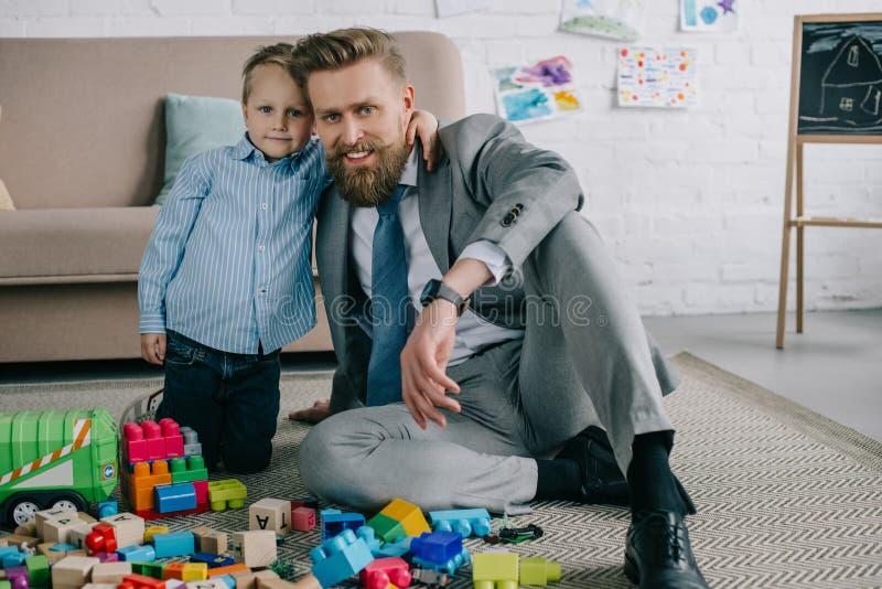 在家拥抱微笑的父亲的小男孩在西装工作和生活中 免版税库存照片