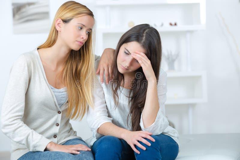 在家拥抱沮丧的朋友的妇女 库存图片