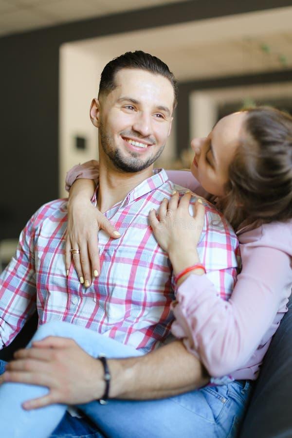 在家拥抱男朋友和微笑的年轻白种人女孩 免版税图库摄影