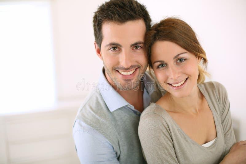 在家拥抱的微笑的夫妇 免版税图库摄影