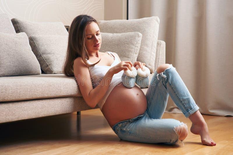 在家拿着小童鞋的孕妇 免版税库存照片