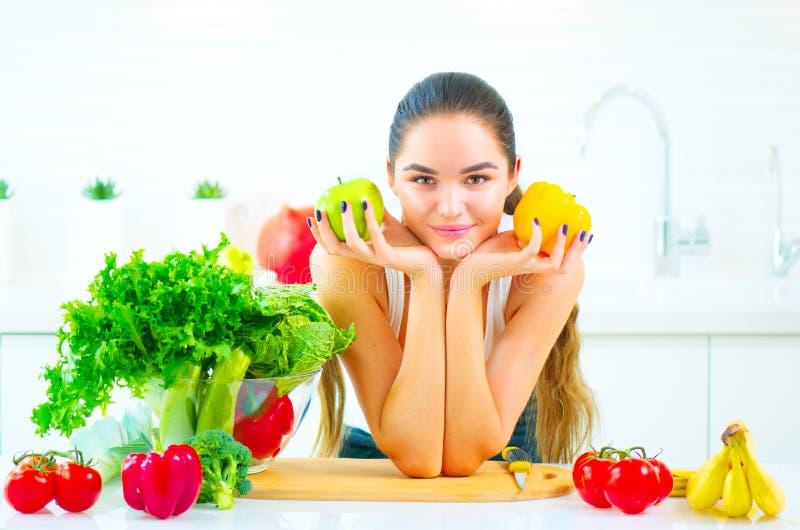 在家拿着新鲜蔬菜和果子的秀丽少妇在她的厨房里 免版税库存照片