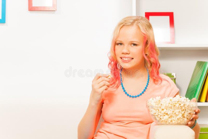 在家拿着碗用玉米花的微笑的女孩 库存照片