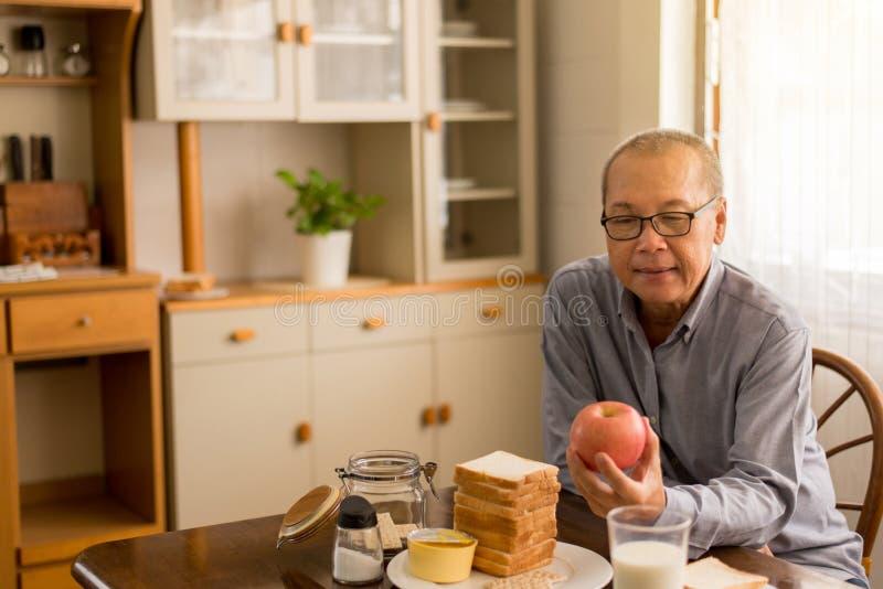 在家拿着红色苹果新鲜水果的资深亚洲人手,年长健康食品概念 免版税库存图片