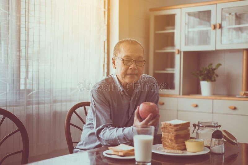 在家拿着苹果新鲜水果的愉快的资深亚洲人手,年长健康食品概念 免版税库存图片