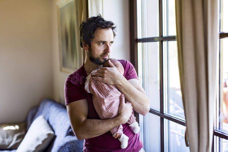 在家拿着他新出生的女婴的年轻父亲 库存图片
