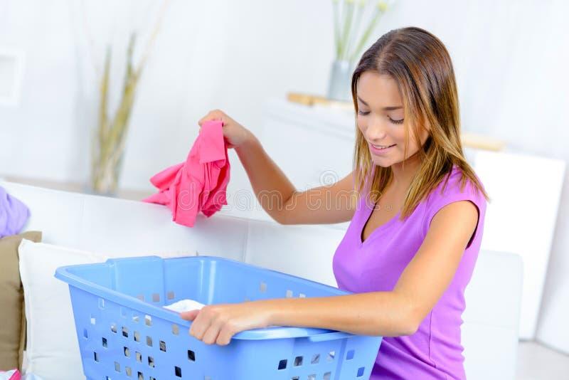 在家排序洗衣店的妇女 库存照片