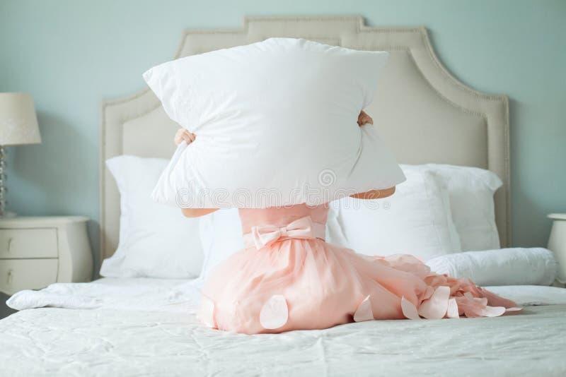 在家掩藏在枕头后的滑稽的儿童女孩 免版税库存图片
