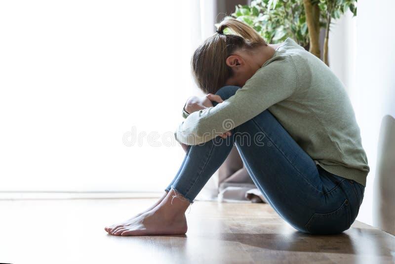 在家掩藏她的在腿之间的不快乐的孤独和沮丧的少妇面孔 免版税库存照片