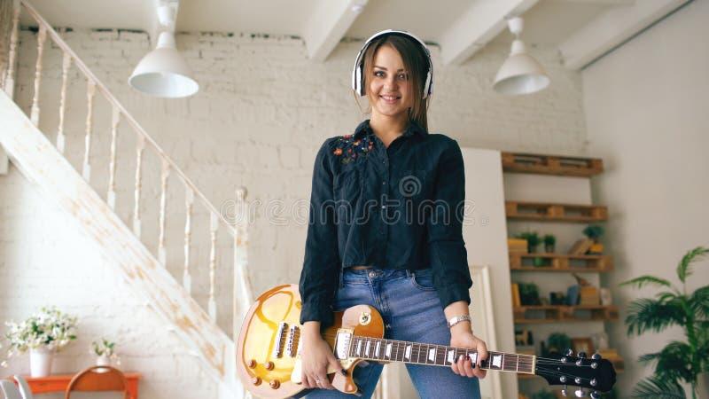 在家摆在与电吉他演播室的耳机的美丽的年轻微笑的女孩户内 免版税图库摄影