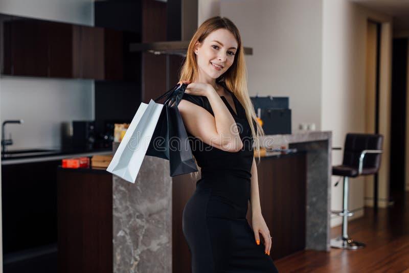 在家摆在与购物袋的微笑的少妇满意对她的购买 免版税库存照片