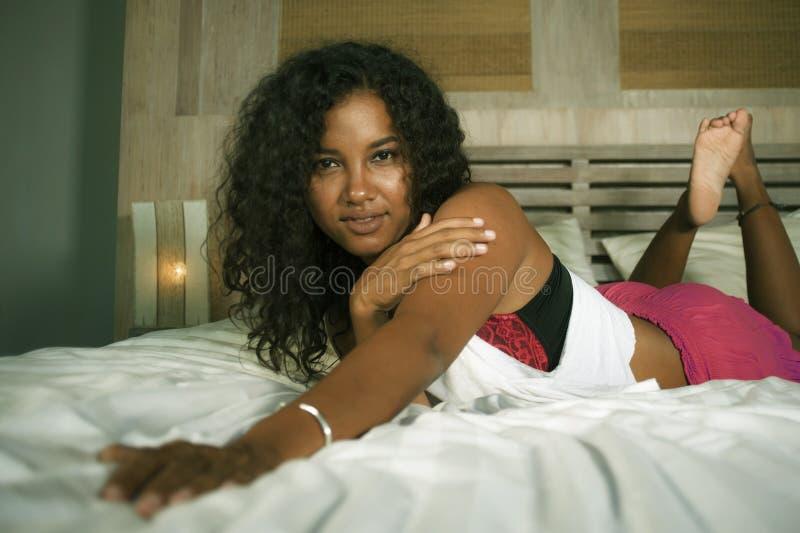 在家摆在性感和嬉戏卧室坐的年轻愉快和华美的黑人拉丁美洲的妇女生活方式画象淘气 免版税库存图片
