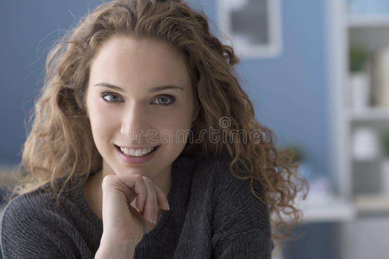 在家摆在美丽的卷曲的年轻女人 免版税库存图片