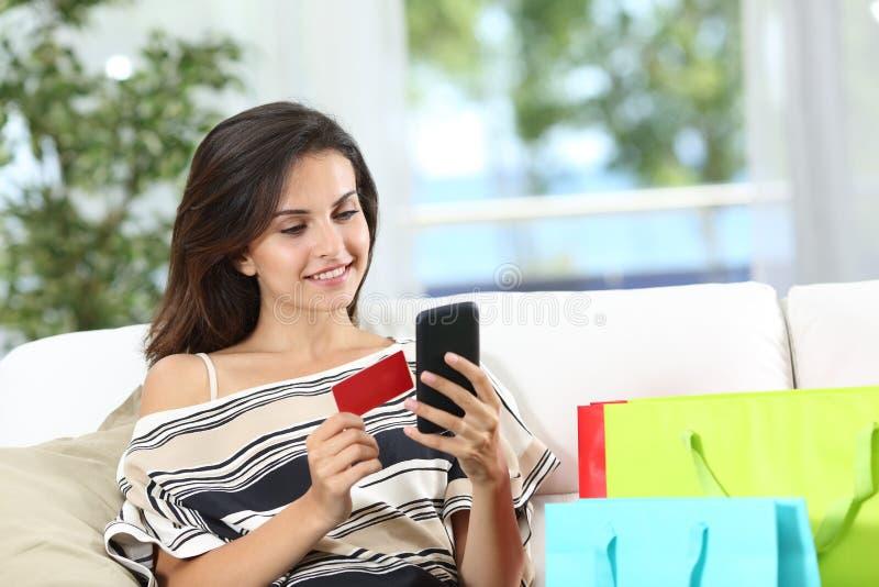 在家支付与信用卡的愉快的网上买家 免版税库存照片