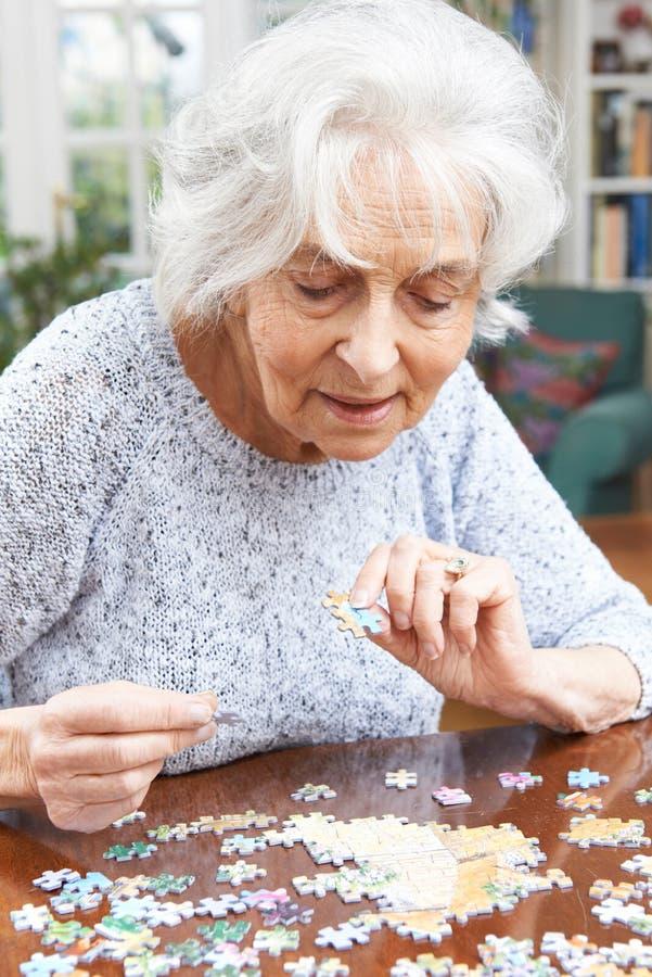 在家放松与七巧板的资深妇女 免版税库存图片