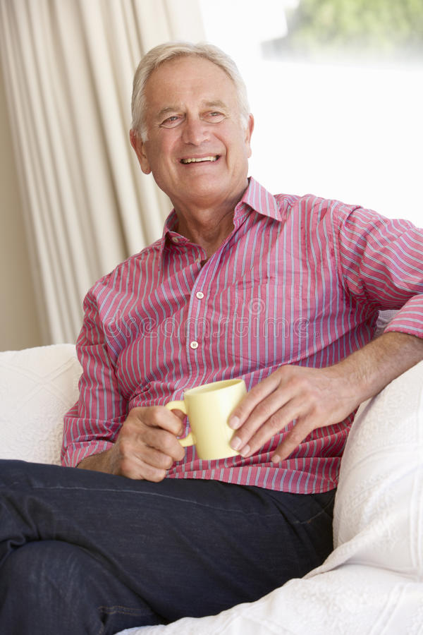 在家放松与热的饮料的老人 免版税库存图片