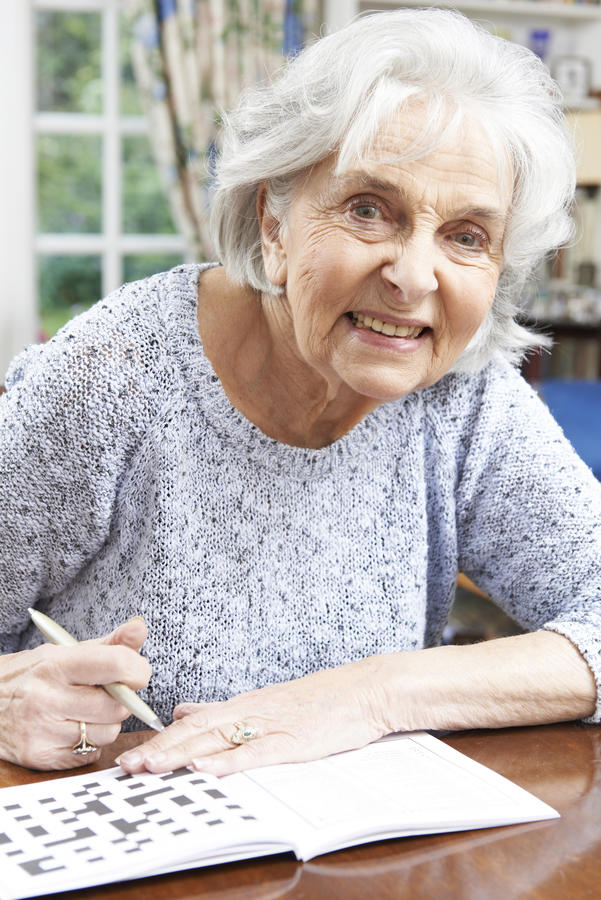 在家放松与纵横填字游戏的资深妇女 免版税库存图片