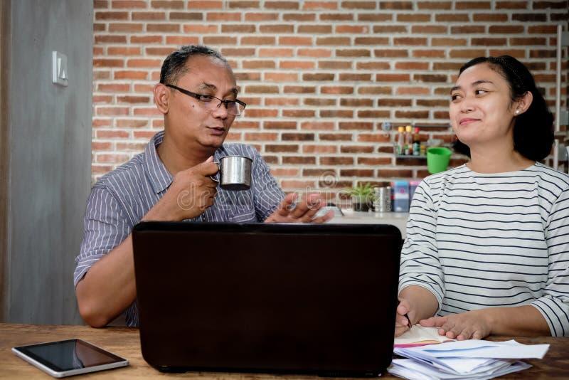 在家放松企业交谈的亚裔工友在厨房办公室 库存照片