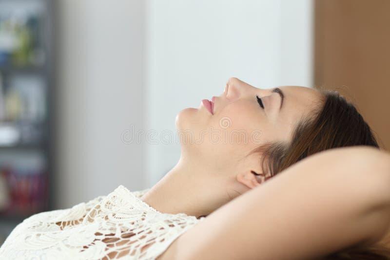 在家放松和睡觉在长沙发的妇女 库存照片