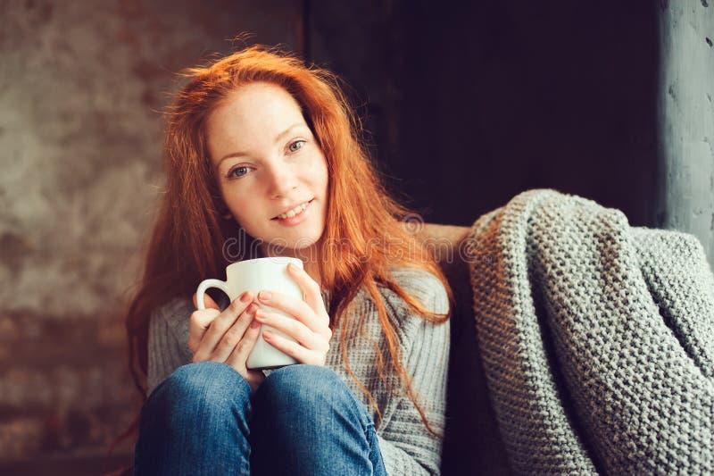 在家放松在与书和杯子的舒适冬天或秋天周末的愉快的红头发人妇女热的茶,坐在软的椅子 库存图片