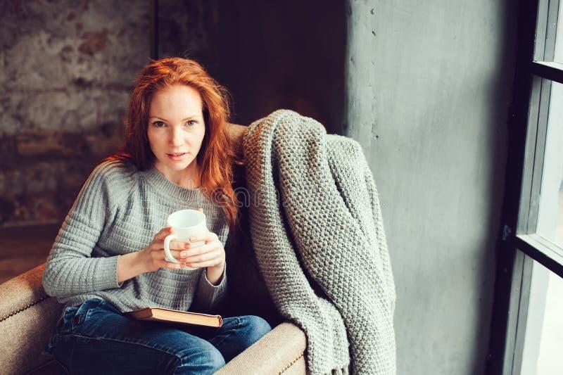 在家放松在与书和杯子的舒适冬天或秋天周末的愉快的红头发人妇女热的茶,坐在软的椅子 图库摄影