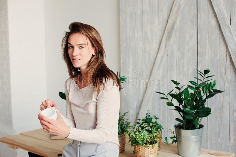 在家放松在与咖啡的懒惰周末早晨的美丽的年轻女性妇女 免版税库存照片