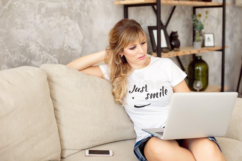 在家放松在她的手提电脑的美丽的年轻女人 库存图片