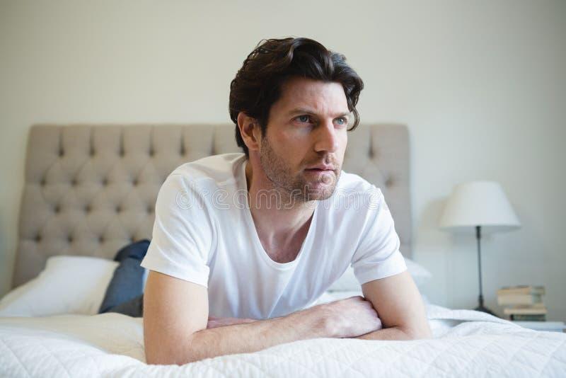 在家放松在床上的人在卧室 免版税库存图片