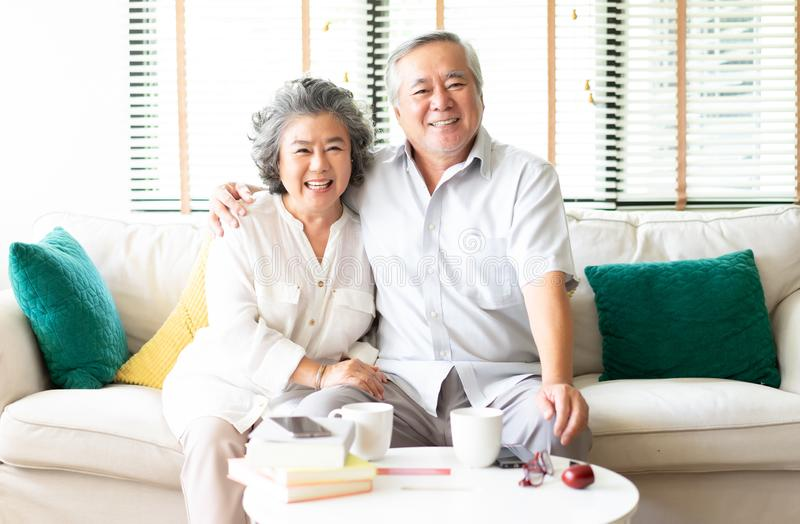 在家放松在有拥抱她的丈夫的妻子的沙发的一对愉快的亚洲资深夫妇的画象微笑对照相机 免版税库存图片
