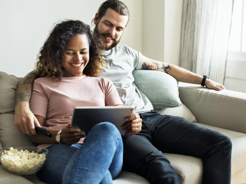 在家放松在沙发生活方式概念的一对年轻夫妇 库存照片