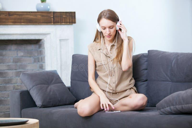 在家放松在沙发的妇女享受在耳机的音乐,微笑 免版税库存图片