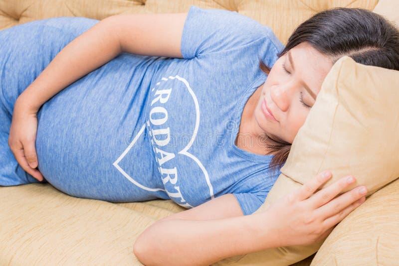 在家放松在沙发的孕妇 免版税图库摄影