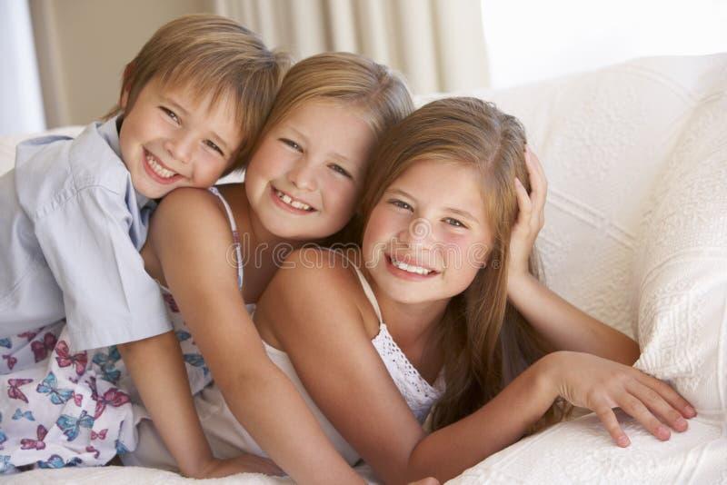 在家放松在沙发的小组孩子 免版税库存图片