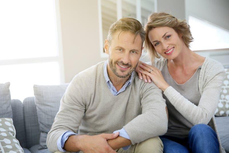 在家放松在沙发的成熟夫妇 库存照片