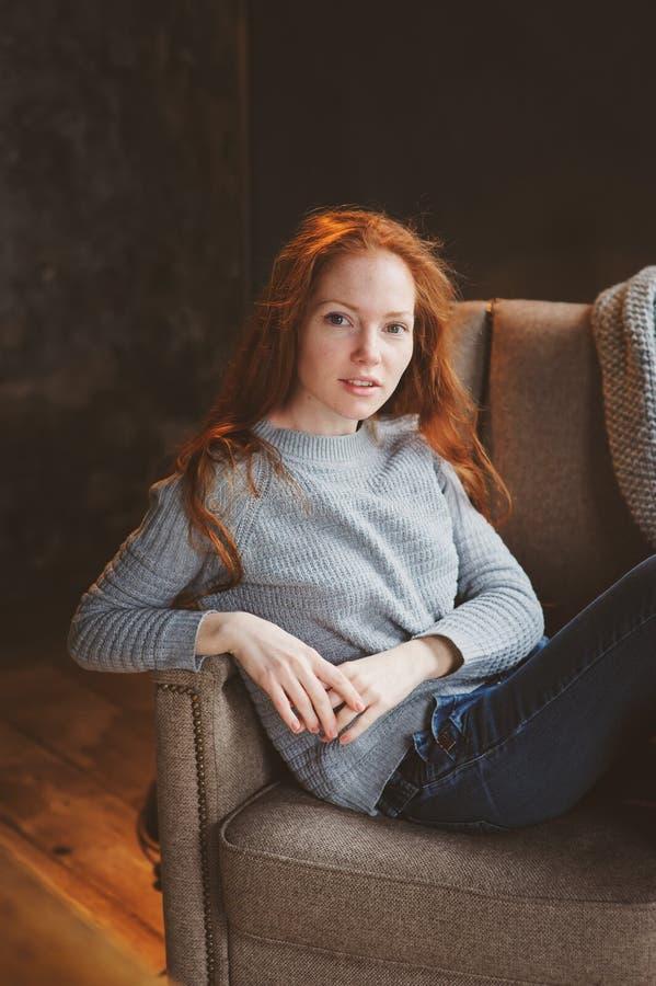 在家放松在舒适椅子的年轻readhead妇女,穿戴在偶然毛线衣和牛仔裤 免版税库存照片