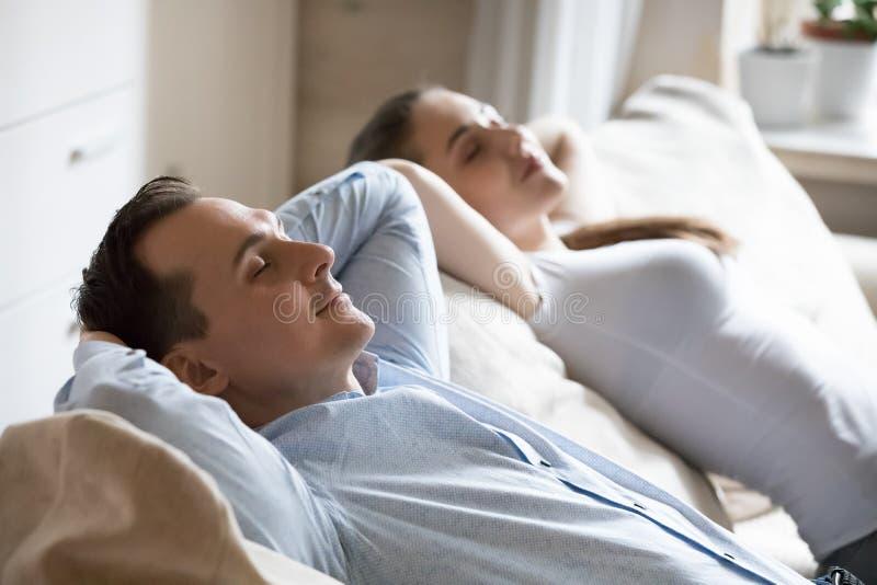 在家放松在软的舒适的沙发的男人和妇女 库存照片