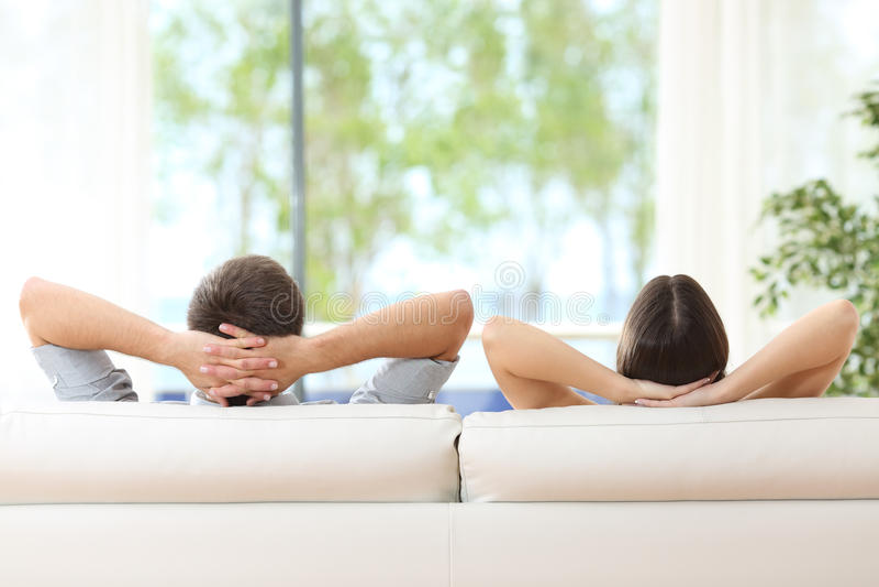 在家放松在长沙发的夫妇 免版税图库摄影