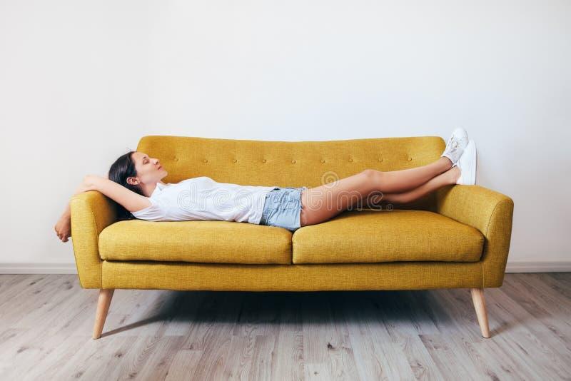 在家放松在长沙发的愉快的年轻女人 库存图片