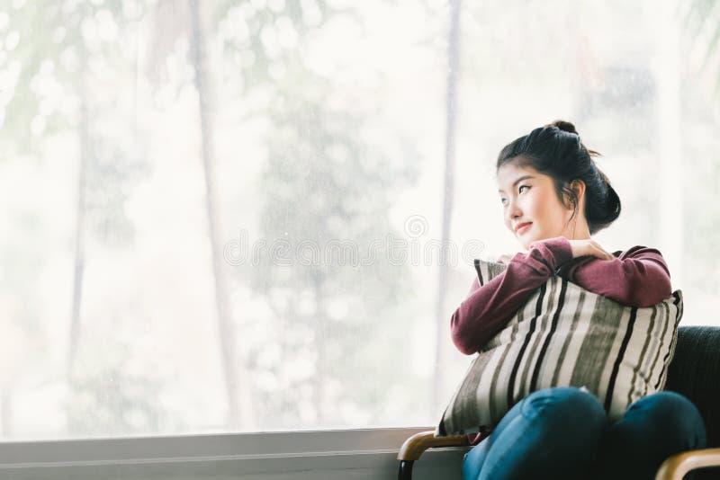 在家放松美丽的年轻亚裔的女孩,单独坐由窗口,看拷贝空间 库存照片