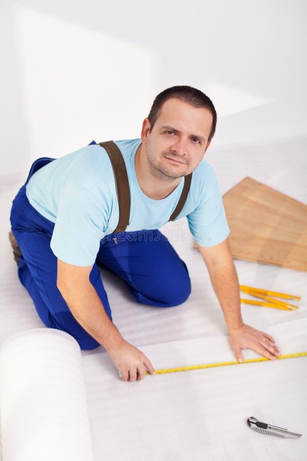 在家放置层压制品的地板的人 免版税库存照片