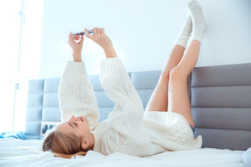 在家放置腿的少妇在床佩带的毛线衣selfie图片的墙壁 免版税库存照片