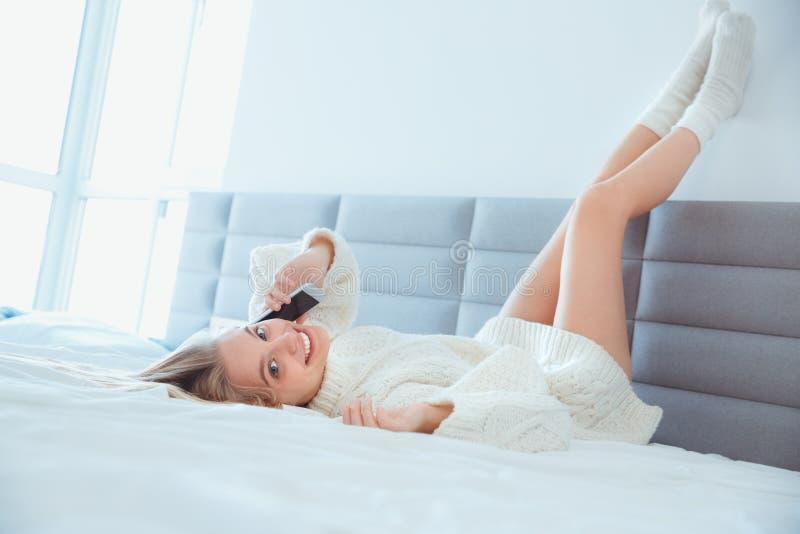 在家放置腿的少妇在看照相机的床佩带的毛线衣电话的墙壁 免版税库存图片