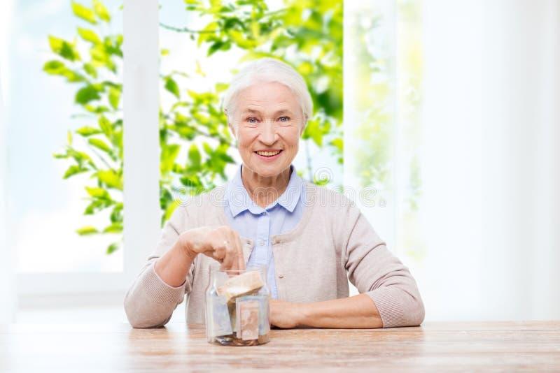 在家放金钱的资深妇女入玻璃瓶子 免版税库存照片