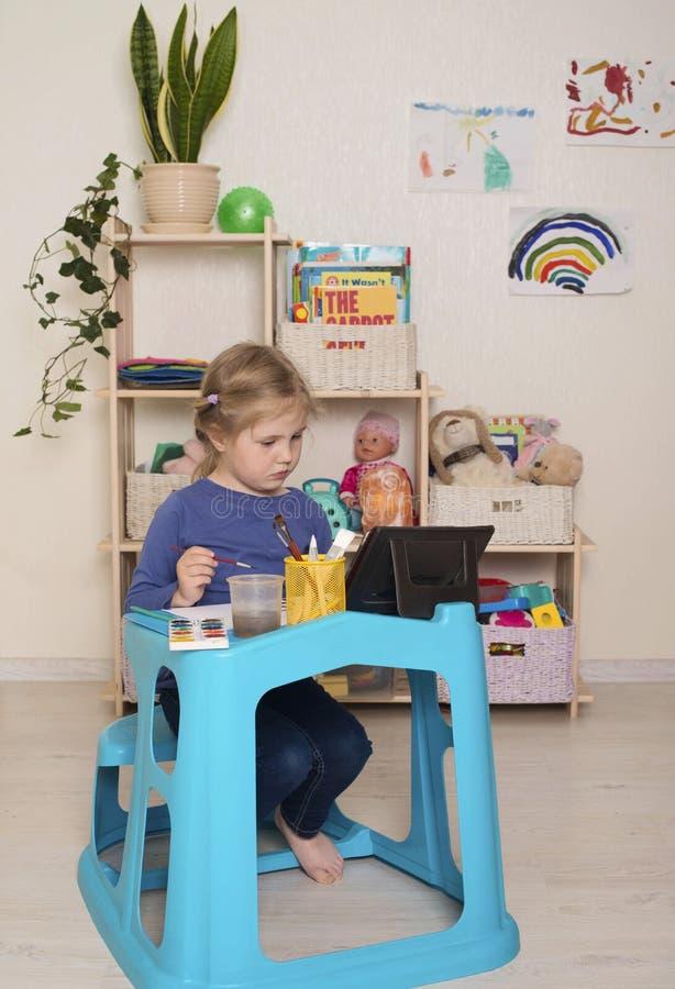 在家教育中,带笔记本的小女孩学习绘画 学龄前儿童利用在线课程 免版税库存图片