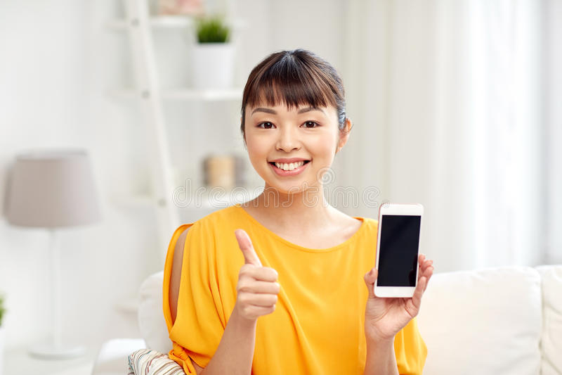在家显示智能手机的愉快的亚裔妇女 免版税库存照片