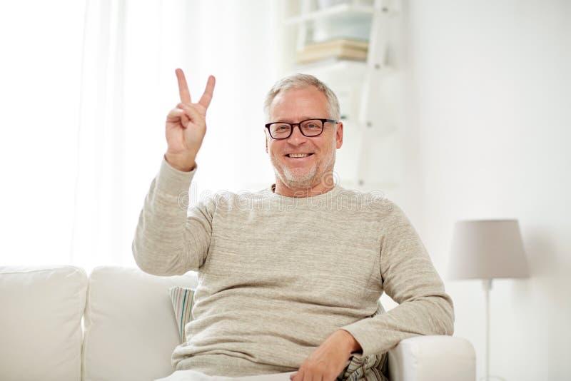 在家显示V形标志的微笑的老人 免版税库存照片