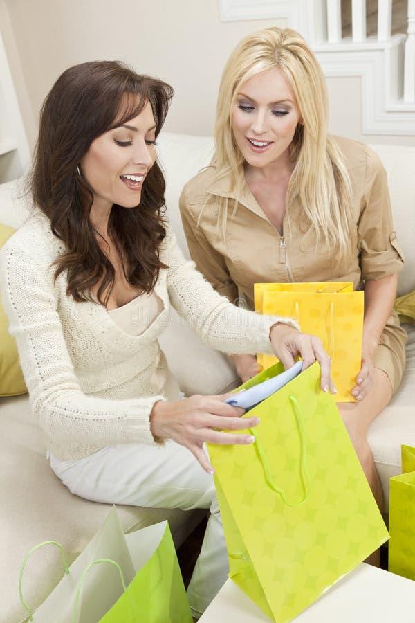 在家查找在购物袋的二个妇女朋友 库存图片