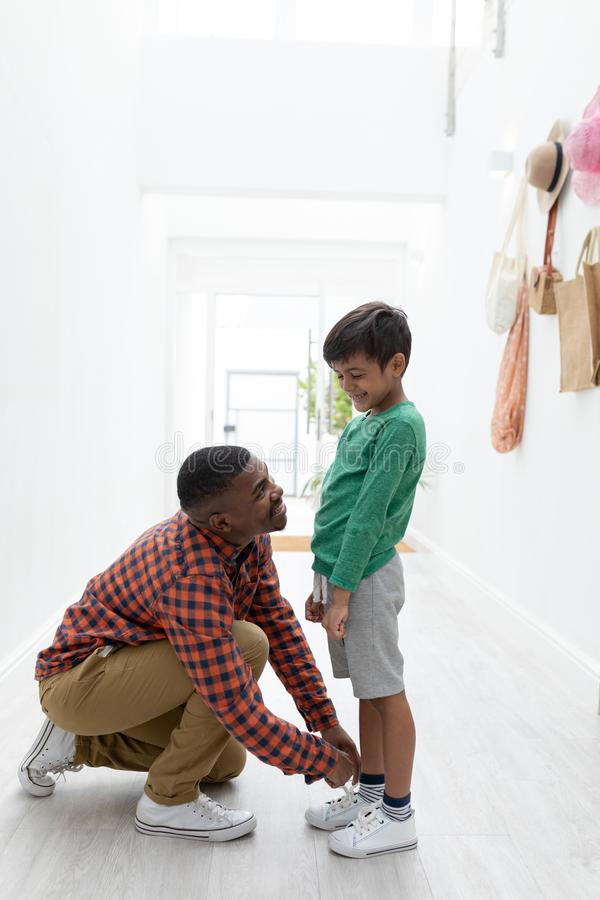 在家栓他的儿子鞋带的父亲 库存照片